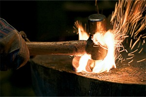 Blacksmith hammering red hot steel on a wooden surface that is catching on fire. Focus is on the hammer and glove.